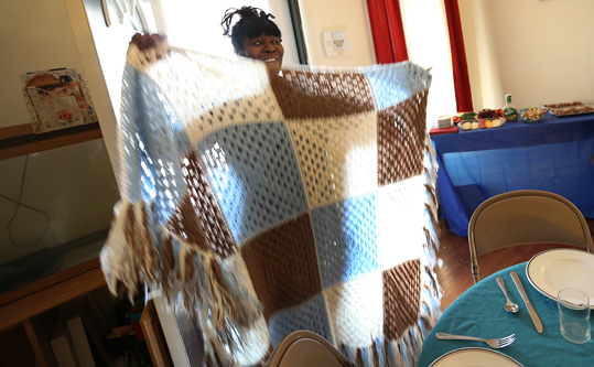 Sarah Killingworth shows a blanket she crocheted, during a dinner at her house, Saturday, March 14, 2015.  She uses her talents for a business.  As part of community outreach, members of Broadway United Methodist Church and the community meet for a meal a