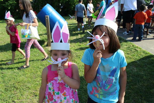 Two little girls dressed as bunnies for an easter egg hunt
