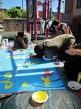 Young men painting a large poster
