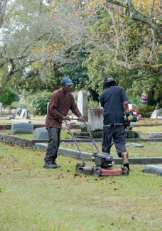 Two men doing landscape work in a cemetry