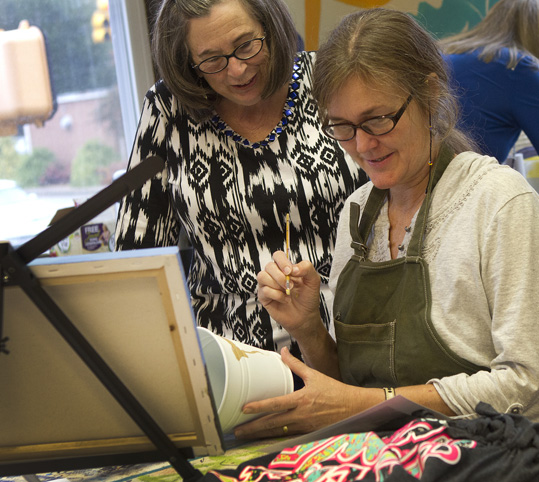 Art teacher helps an adult student at the Triune Mercy Center