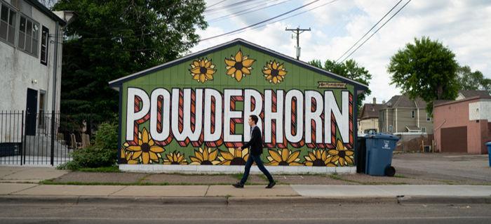 Tyler Sit walks in front of a mural in the Powderhorn neighborhood of Minneapolis