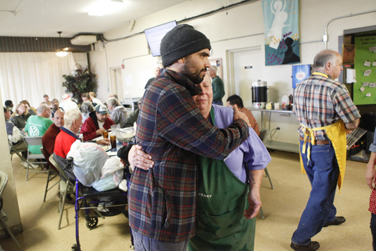 Haywood Street Congregation Pastor Brian Combs hugs volunteer Trudy Gordon.
