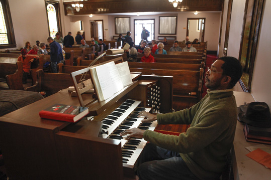 Staff organist Edward Clarence Smith plays as the congregation gathers to worship.